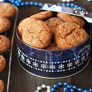 Vegan Gluten Free Gingerbread Cookies sitting in a metallic Christmas tin.