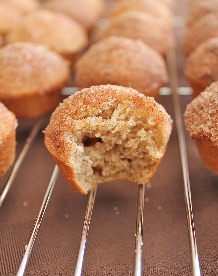 Old Fashioned Cake Doughnut Mini Muffins on a metal cooling rack, the muffin at the forefront of the image has a bite taken out of it.