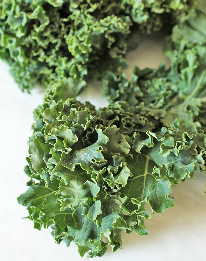Raw kale leaves on a table to make easy kale chips.