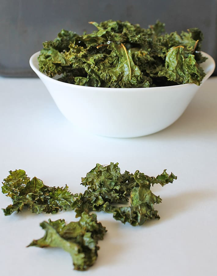 Easy kale chips in a white bowl on a table.