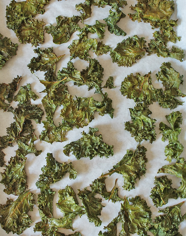 Freshly baked easy kale chips on a baking sheet.