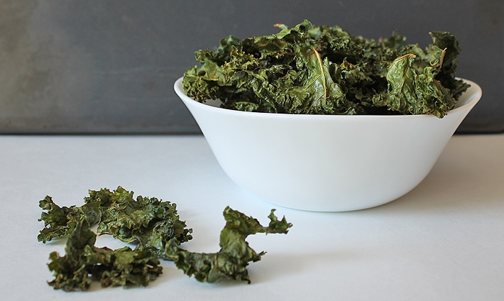 Easy Kale Chips in a white bowl, a few kale chips are in the forefront on the table.