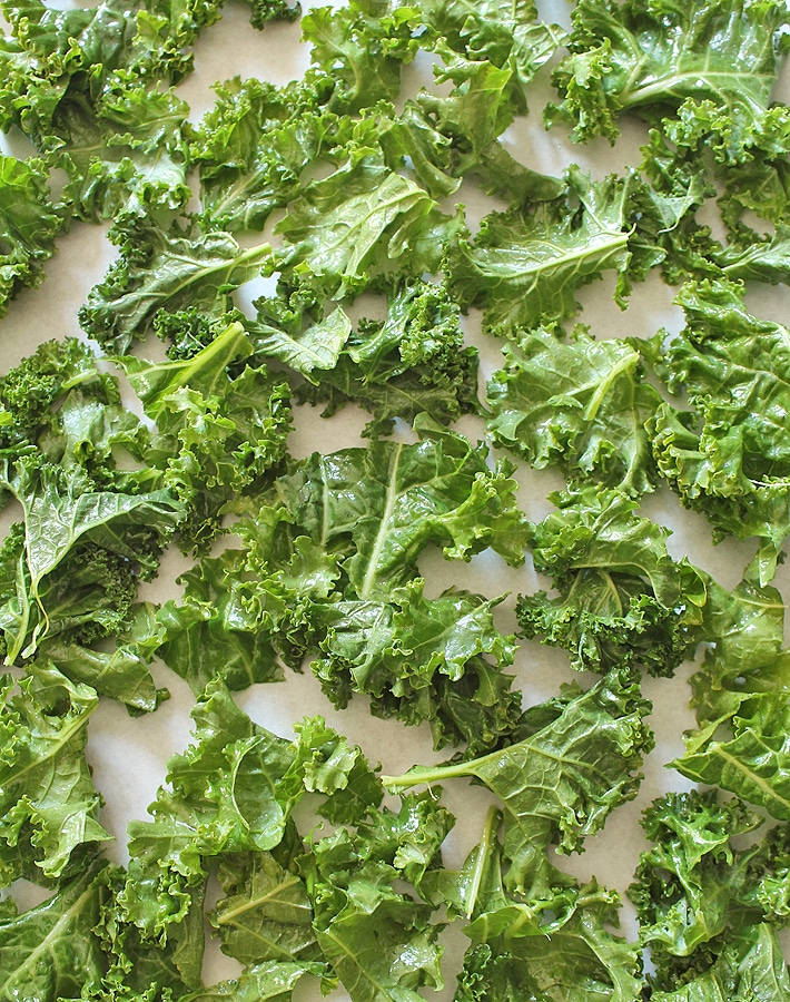 Raw kale leaves on a baking sheet to make Easy Kale Chips.