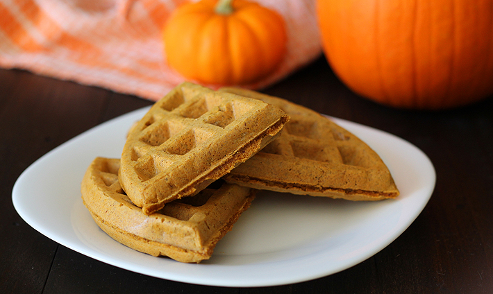 Vegan Gluten Free Pumpkin Spice Waffles on a white plate, fresh pumpkin are on the table behind the plate.