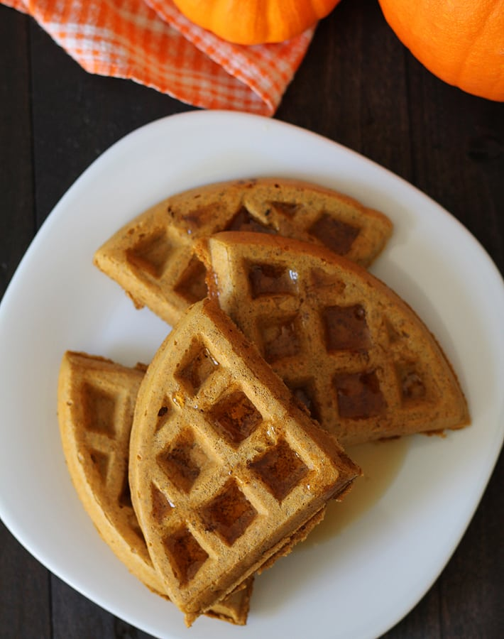 Overhead shot of Vegan Gluten Free Pumpkin Spice Waffles on a white plate.
