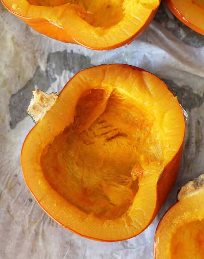 How to Make Homemade Pumpkin Puree - Cooked sigar pumpkins lying cut side up on a parchment lined baking sheet.