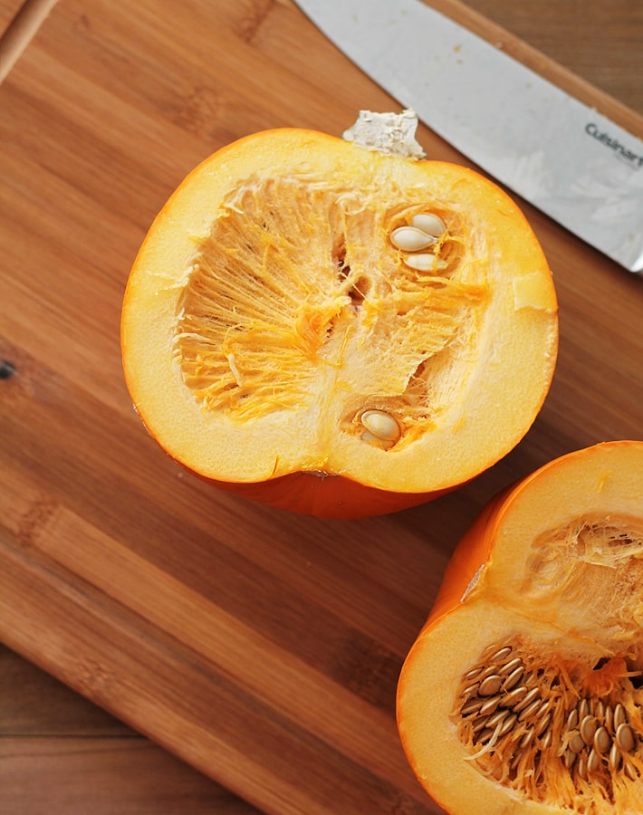 How to Make Homemade Pumpkin Puree - Two halves of a sugar pumpkin on a cutting board.