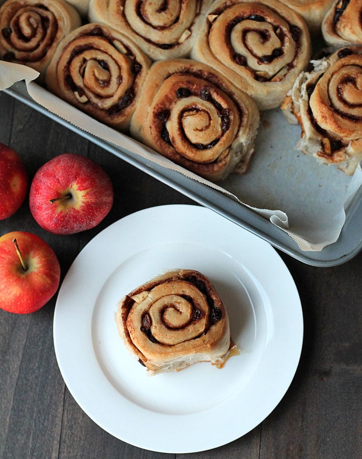 Overhead shot of Vegan Apple Raisin Cinnamon Rolls in a parchment lined baking pan with fresh red apples in front of the pan and one roll on a white plate in front of the pan.