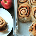 Vegan Apple Raisin Cinnamon Rolls sitting in a baking pan on the right and one roll is sitting on a white plate to the left.