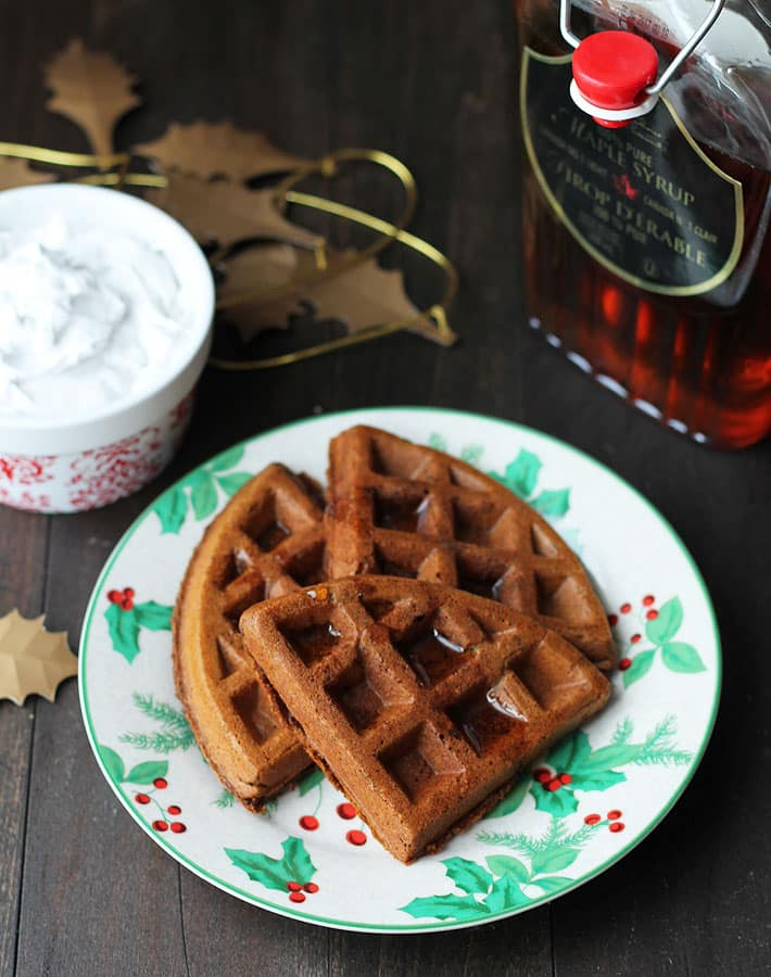 Overhead shot of Vegan Gluten Free Gingerbread Waffles on a plate with a bottle of maple syrup to the right.