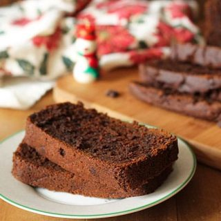 Vegan Gluten Free Gingerbread Loaf slices on a small plate, rest of the load sits in the background.