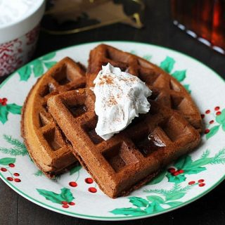 Vegan Gluten Free Gingerbread Waffles on a Christmas plate and coconut whipped cream on top.