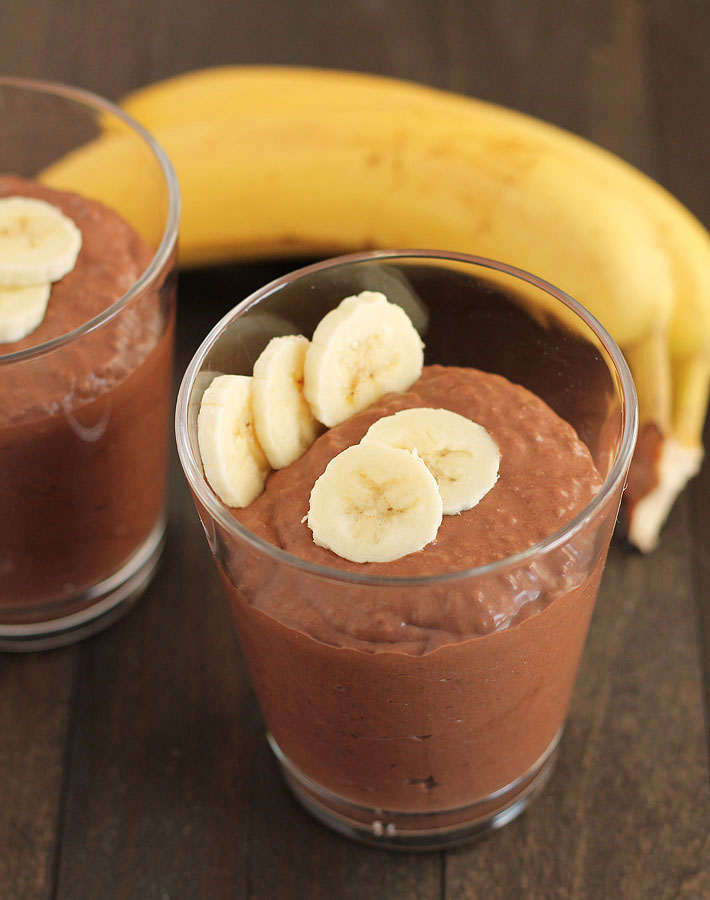 A clear cup filled with Chocolate Banana Coconut Chia Pudding sitting on a wooden table, two ripe bananas sit behind the cup.