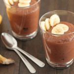 Chocolate Banana Coconut Chia Pudding in a glass with sliced bananas on top for garnish, two spoons and two bananas sit to the left and another glass of pudding is behind.