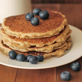A stack of four Easy Vegan Gluten Free Pancakes on a white plate, the pancakes are garnished with fresh blueberries, everything is sitting on a brown wooden table.