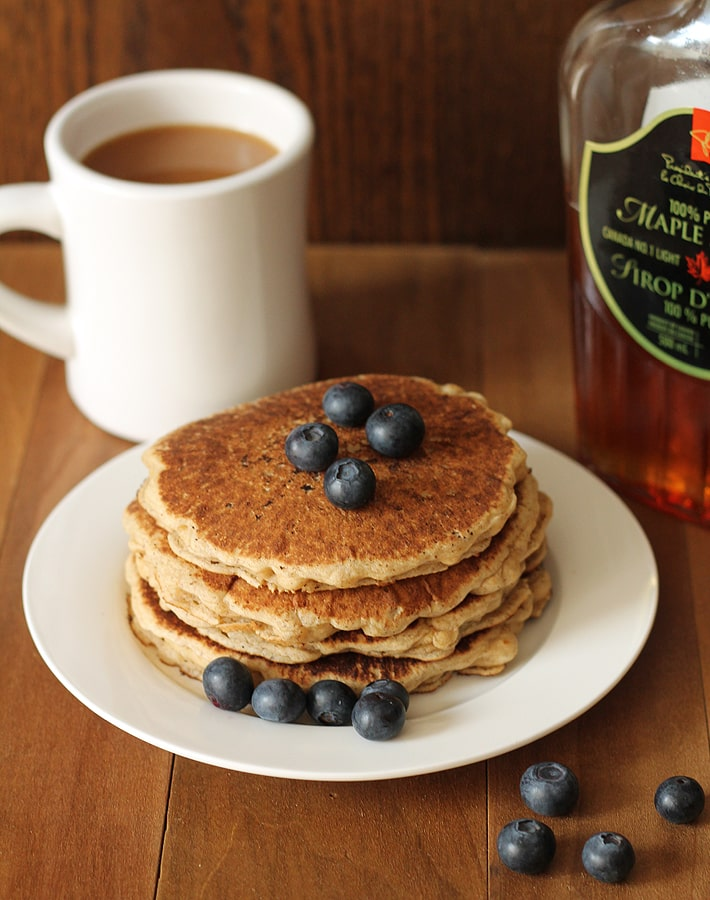 A stack of four Easy Vegan Gluten Free Pancakes on a white plate sitting on a brown wooden table, fresh blueberries are on top of the pancakes, a white mug of coffee sits in the background and a bottle of maple syrup sits to the right.