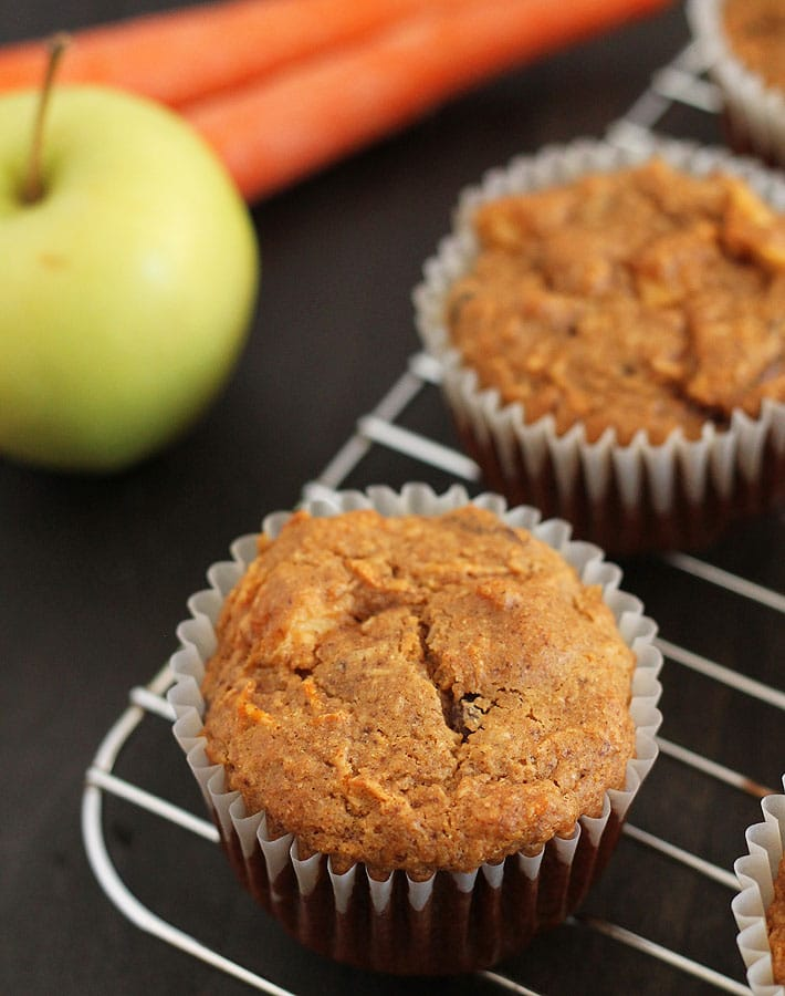 Vegan Gluten Free Morning Glory Muffins on a wood table, muffins are sitting on a steel cooling rack.