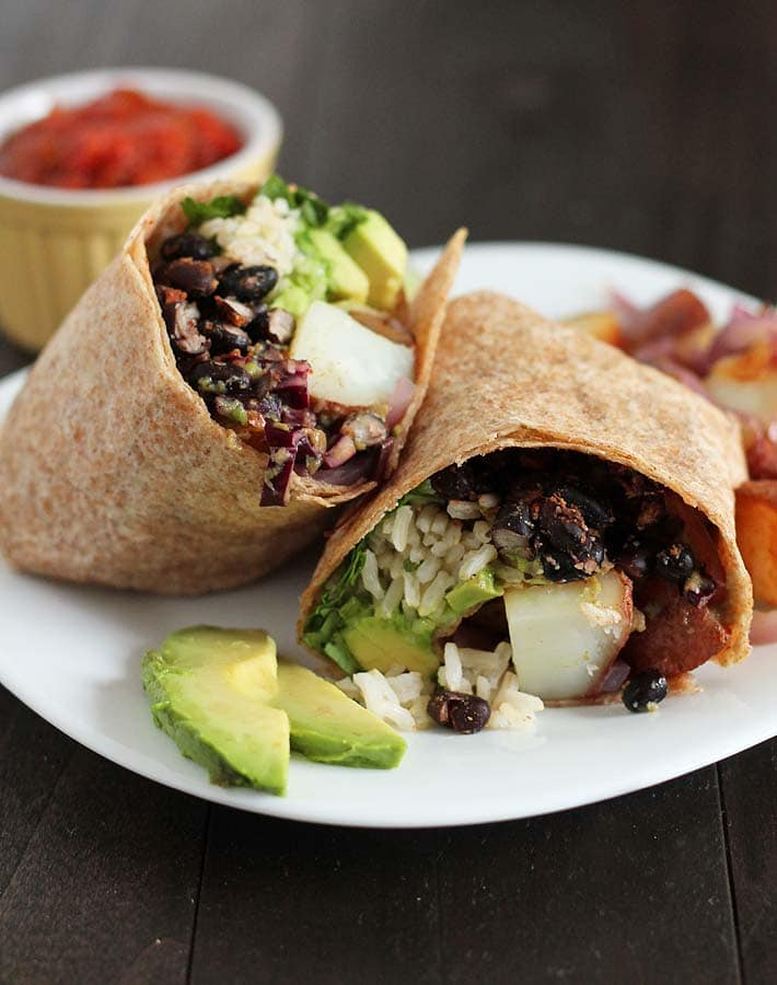 Vegan Breakfast Burrito on a white plate with avocado slices on the side of the plate, a small cup of salsa sits behind the plate.