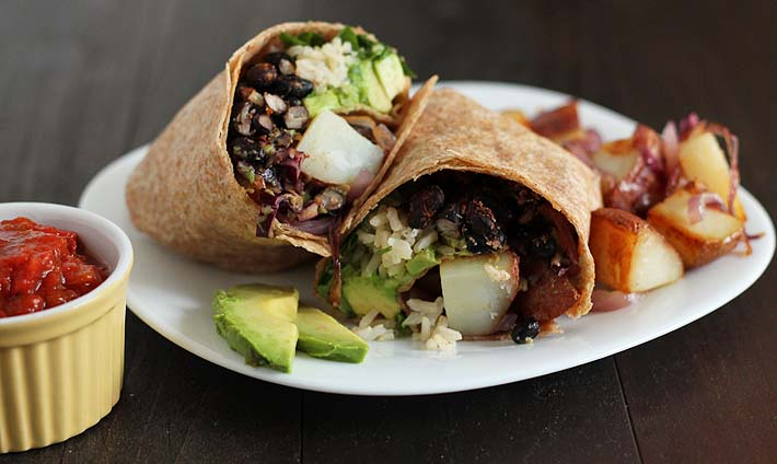 Vegan Breakfast Burrito on a small white plate, fried potatoes and avocado slices sit on the side of the burrito and a cup of salsa sits to the left of the plate.