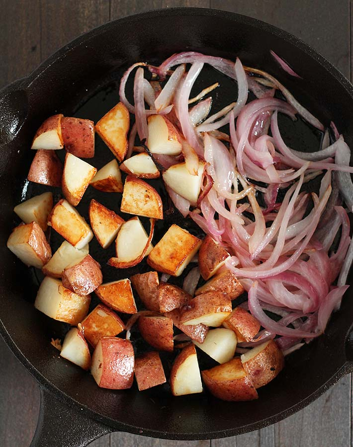 A cast iron pan with fried red potatoes and red onions that will be used to make a vegan breakfast burrito.