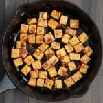 Overhead shot of fried tofu in a cast iron pan