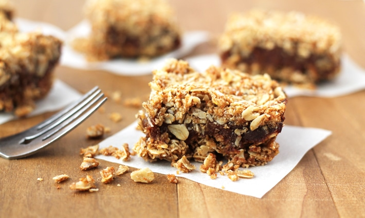 Three Vegan Date Squares on parchment squares on a brown wood table, a fork sits to the left.