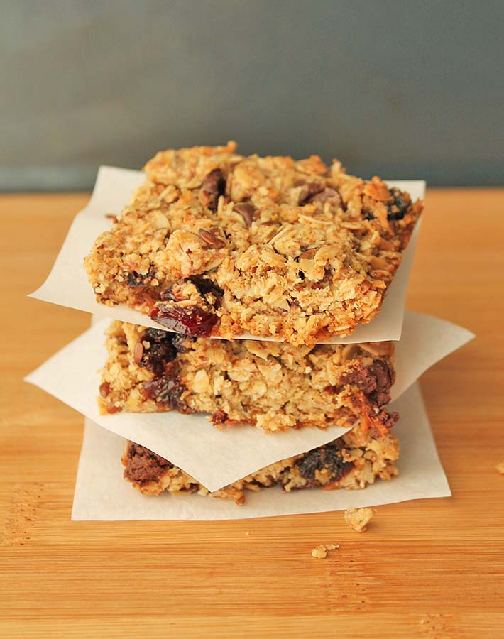 Granola Squares sticked on top of each other separated by parchment paper.