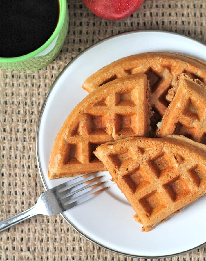 Apple cinnamon waffles on a plate, plate sits on a brown burlap placemat.