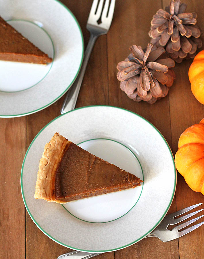 Overhead shot of a slice of quick and easy vegan pumpkin pie on a green rimmed white plate.