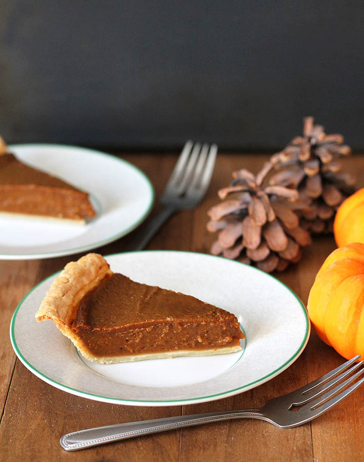 Two slices of Quick and Easy Vegan Pumpkin Pie sitting on small white plates, forks are in front and to the sides of each plate.