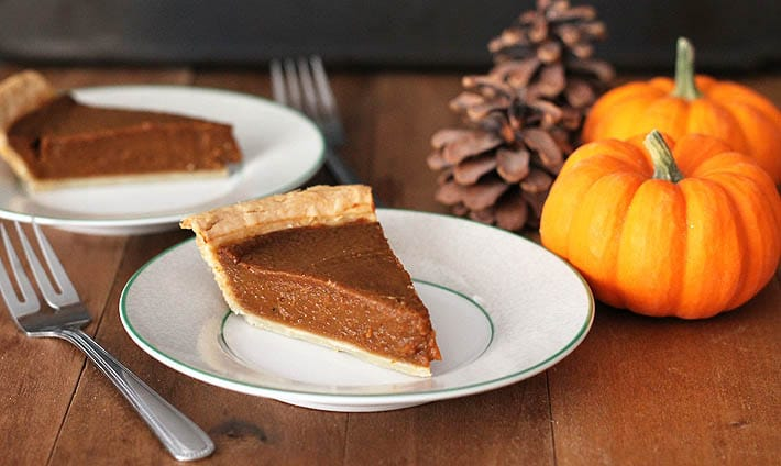 A close up shot of a slice of quick and easy vegan pumpkin pie sitting on a plate, another slice is sitting on another plate in the background.