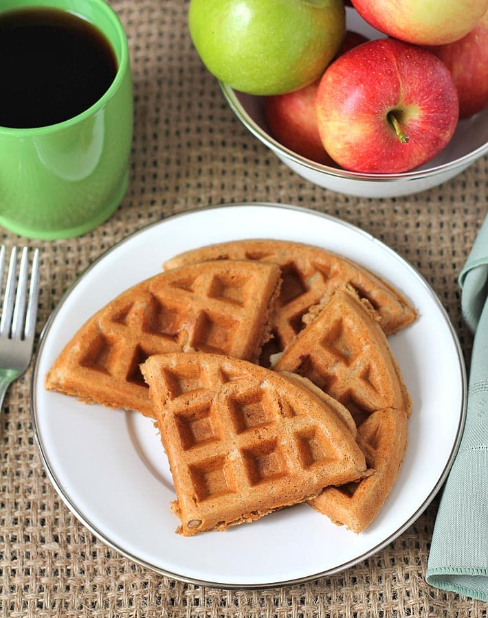 Overhead shot of apple cinnamon waffles on a plate, a cup of coffee sits to the left and a bowl of fresh apples sits behind the plate.