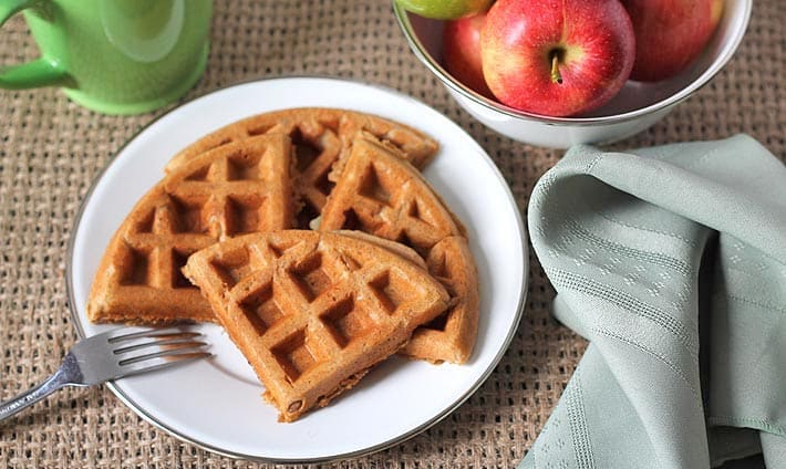 Apple cinnamon waffles on a white plate with a fork on the side of the plate.