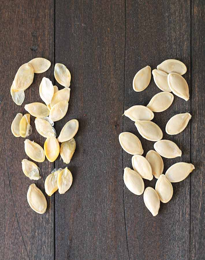 How to Roast Pumpkin Seeds - Pumpkin seeds on a dark wood table, seeds on the left are not suitable for roasting, seeds on the right are suitable.