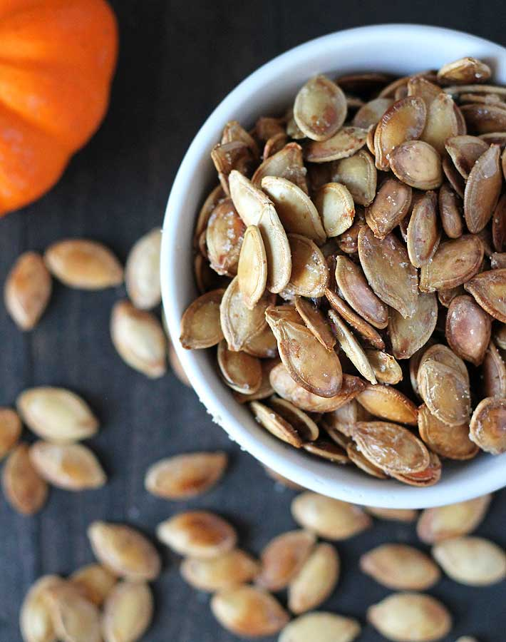 How to Roast Pumpkin Seeds - Overhead shot of roasted pumpkin seeds in a white bowl.