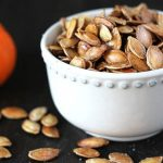 How to Roast Pumpkin Seeds - Roasted pumpkin seeds in a small white bowl on a dark wooden table, a small pumpkin is sitting off to the left of the bowl, some seeds are scattered on the table.