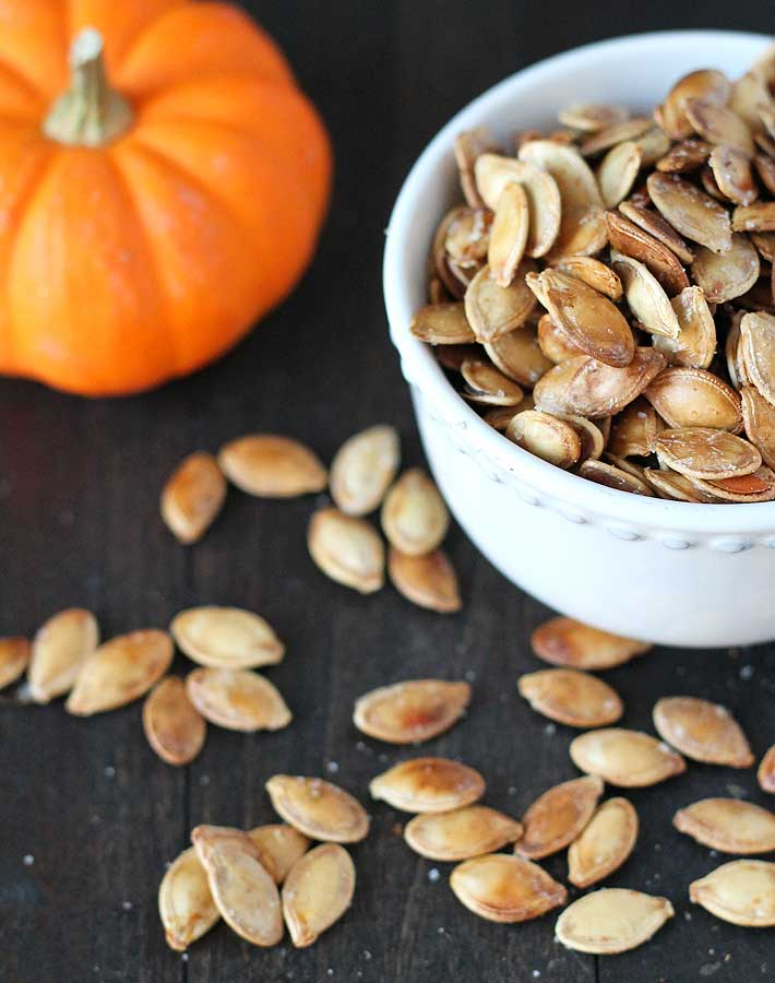 How to Roast Pumpkin Seeds - Roasted pumpkin seeds in a white bowl on a dark wooden table, some seeds are scattered on the table.