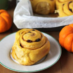 Vegan Pumpkin Cinnamon Rolls in a parchment lined baking pan with small pumpkins sitting on the side and in front of the pan.