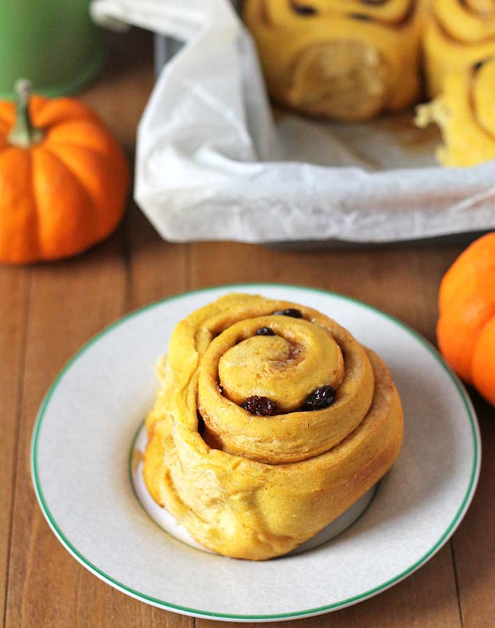 Vegan Pumpkin Cinnamon Rolls in a baking pan sitting in the background and one roll sitting on a white plate.