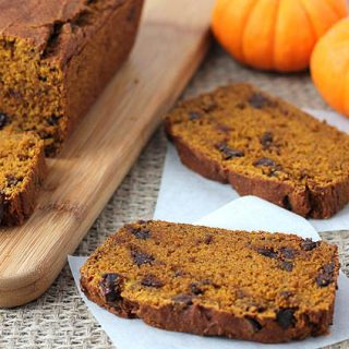 A loaf of Vegan Gluten Free Pumpkin Chocolate Chip Bread with three slices sliced out of it, two slices are sitting off to the side and two small pumpkins sitting behind it.