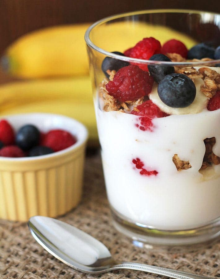 A Banana Berry Granola Yogurt Parfait sitting on a burlap placemat, a spoon sits in front of the clear glass holding the parfait and a small yellow cup of berries sits off to the left.
