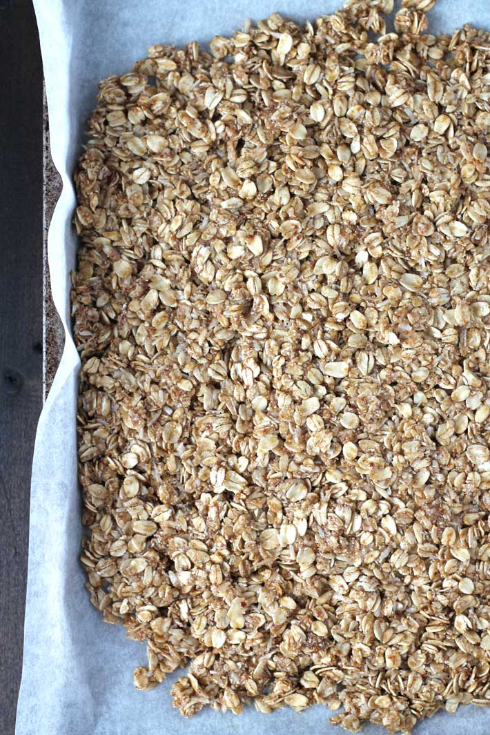 Overhead shot of a sheet of nut free granola just about to go into the oven.