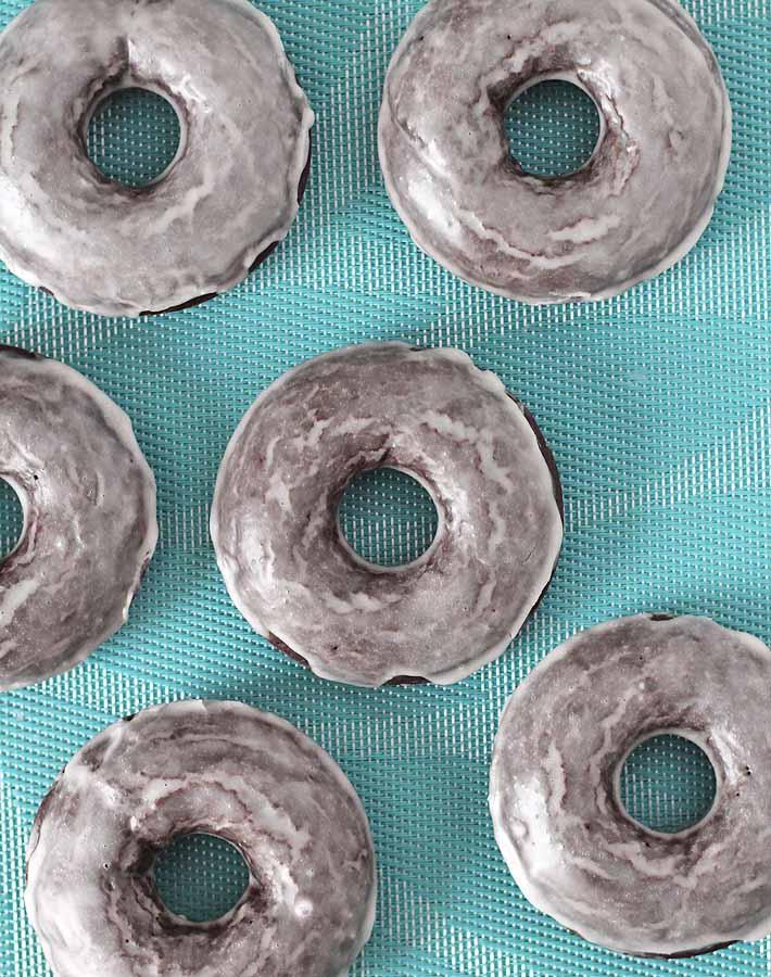 Six Vegan Gluten Free Baked Chocolate Doughnuts on a light blue table cloth.