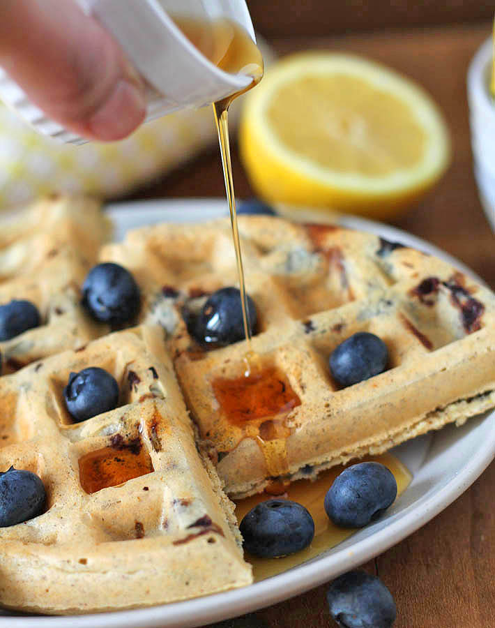 Maple syrup being poured onto Vegan Gluten Free Lemon Blueberry Waffles.
