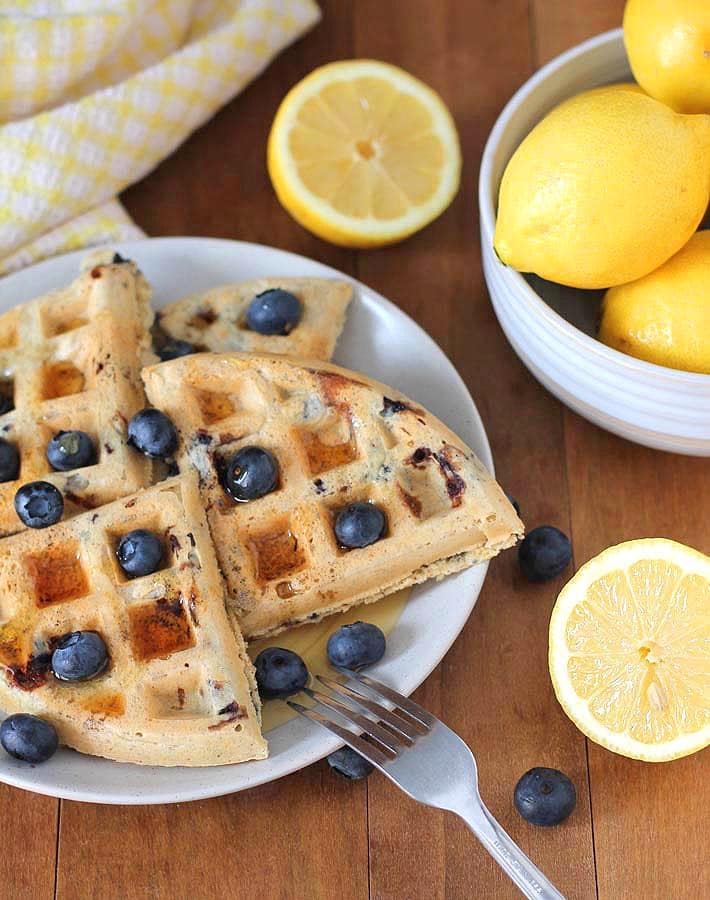 Vegan Gluten Free Lemon Blueberry Waffles garnished with fresh blueberries on a plate.