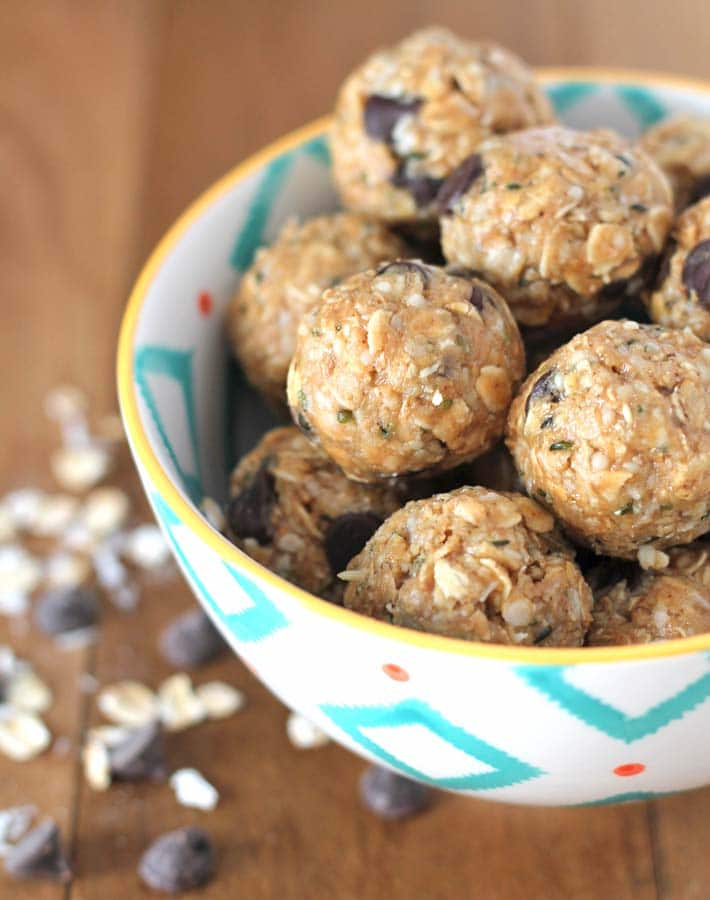 No Bake Peanut Butter Coconut Balls in a patterned bowl on a wood table.