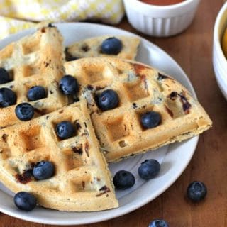 Four pieces of Vegan Gluten Free Lemon Blueberry Waffles on a plate.