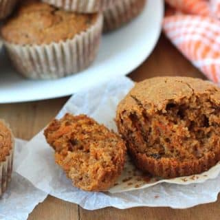 Carrot Ginger Muffins on a brown table, the muffin in the front has a chunk taken out of it.