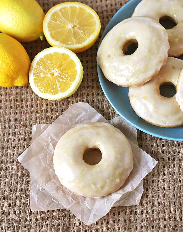 Overhead shot of Vegan Baked Lemon Doughnuts and fresh lemons on a burlap placemat.