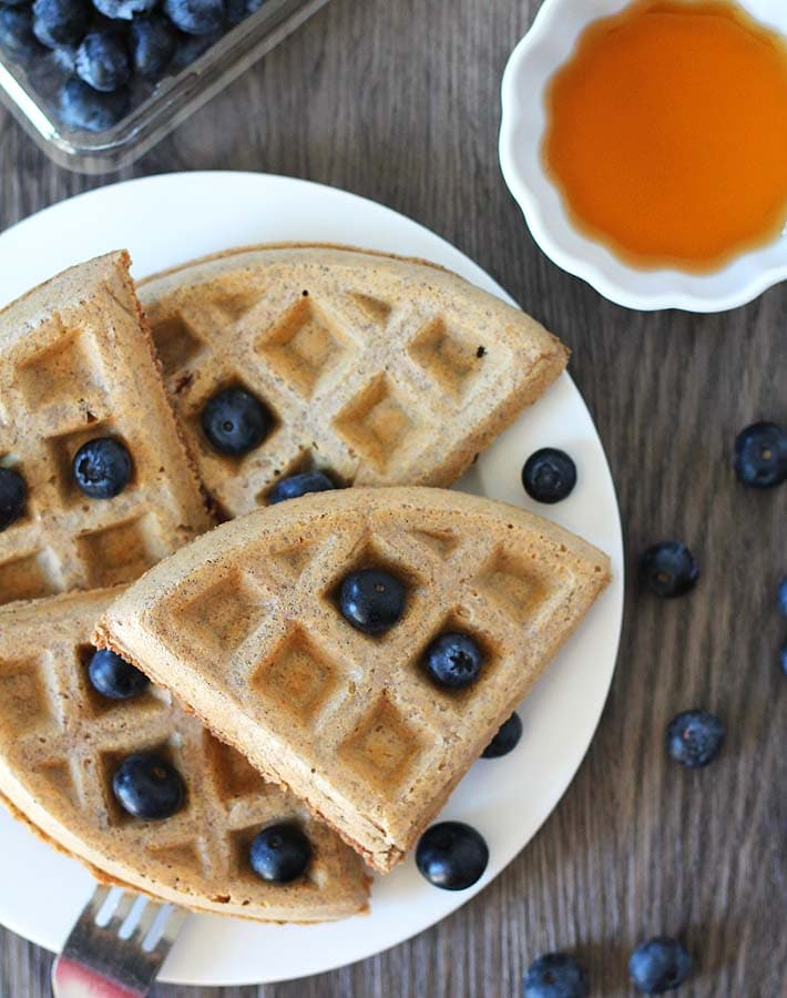 Overhead shot of Easy Vegan Gluten Free Waffles on a white plate sitting on a wood table, waffles are garnished with fresh blueberries, a container of blueberries sits behind the plate and a cup of maple syrup sits to the right.